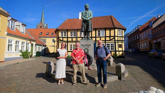 De tre Ørsted-tegneserieskabere foran statuen af H.C. Ørsted på Gaasetorvet i Rudkøbing.